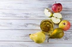 Сок в стеклянном и зрелые яблоки и груши на деревянном столе Стоковое Изображение RF