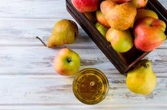 Сок в стеклянном и зрелые яблоки и груши на деревянном столе Стоковые Изображения RF