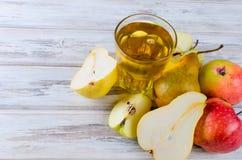 Сок в стеклянном и зрелые яблоки и груши на деревянном столе Стоковое Изображение