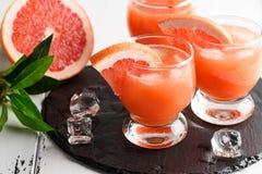 Сок грейпфрута и зрелые грейпфруты на деревянной предпосылке стоковое фото