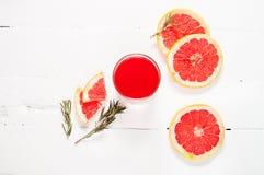 Сок грейпфрута и зрелые грейпфруты на деревянной предпосылке Стоковые Изображения RF