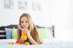 Сок девушки выпивая и ослаблять в спальне Стоковая Фотография RF