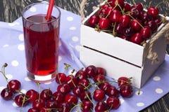 Сок и красные вишни в деревянной коробке Стоковые Изображения