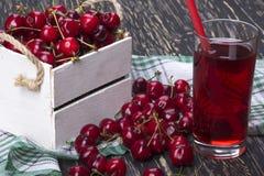 Сок и красные вишни в деревянной коробке Стоковая Фотография RF