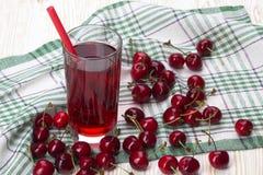 Сок и красные вишни на деревянном столе Стоковая Фотография
