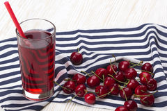 Сок и красные вишни на деревянном столе Стоковое Изображение