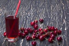 Сок и красные вишни на деревянном столе Стоковые Изображения