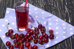 Сок и красные вишни на деревянном столе Стоковая Фотография RF