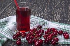 Сок и красные вишни на деревянном столе Стоковое фото RF