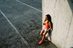 Сок и отдыхать вытрезвителя расслабленной sporty молодой женщины выпивая стоковые изображения