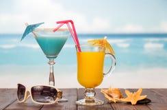 Сок коктеиля и стекла с зонтиками, соломами, солнечными очками, sta Стоковые Фотографии RF
