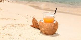 Сок коктеиля кокоса оранжевый на тропическом пляже песка Стоковые Фотографии RF