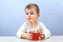 Сок милого мальчика выпивая на свете - голубой предпосылке Симпатичный сок виноградины питья ребенк Стоковые Фотографии RF
