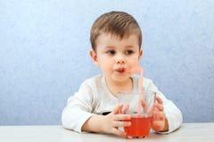 Сок милого мальчика выпивая на свете - голубой предпосылке Симпатичный сок виноградины питья ребенк Стоковые Изображения RF