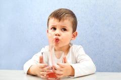 Сок милого мальчика выпивая на свете - голубой предпосылке Симпатичный сок виноградины питья ребенк Стоковое Фото