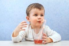 Сок милого мальчика выпивая на свете - голубой предпосылке Симпатичный сок виноградины питья ребенк Стоковое фото RF