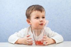 Сок милого мальчика выпивая на свете - голубой предпосылке Симпатичный сок виноградины питья ребенк Стоковое Изображение RF