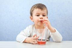 Сок милого мальчика выпивая на свете - голубой предпосылке Симпатичный сок виноградины питья ребенк Стоковая Фотография RF