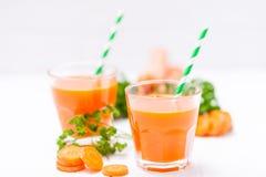 Сок моркови в красивых стеклах, отрезанных оранжевых овощах и зеленой петрушке на белой деревянной предпосылке помеец питья свежи Стоковое Фото