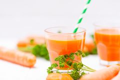 Сок моркови в красивых стеклах, отрезанных оранжевых овощах и зеленой петрушке на белой деревянной предпосылке помеец питья свежи Стоковое Изображение RF