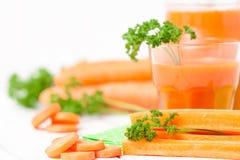 Сок моркови в красивых стеклах, отрезанных оранжевых овощах и зеленой петрушке на белой деревянной предпосылке помеец питья свежи Стоковые Фото