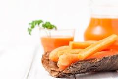 Сок моркови в красивых стеклах, отрезанных оранжевых овощах и зеленой петрушке на белой деревянной предпосылке помеец питья свежи Стоковые Фотографии RF
