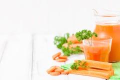 Сок моркови в красивых стеклах, отрезанных оранжевых овощах и зеленой петрушке на белой деревянной предпосылке помеец питья свежи Стоковое Изображение