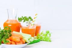 Сок моркови в красивых стеклах, отрезанных оранжевых овощах и зеленой петрушке на белой деревянной предпосылке помеец питья свежи Стоковые Изображения