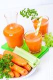 Сок моркови в красивых стеклах, отрезанных оранжевых овощах и зеленой петрушке на белой деревянной предпосылке помеец питья свежи Стоковые Изображения RF
