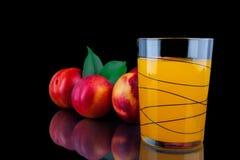 Сок персика в стекле на черной предпосылке Стоковое Изображение RF