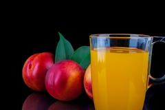 Сок персика в стекле на черной предпосылке Стоковое Изображение