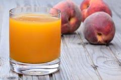 Сок персика в стекле на таблице Стоковые Фото
