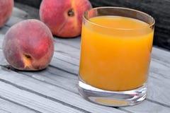 Сок персика в стекле на таблице Стоковая Фотография