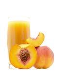 Сок персика в стекле при отрезанный персик близко изолированный на белизне Стоковая Фотография