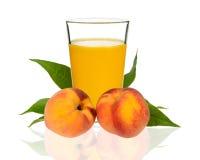 Сок персика в стекле с персиками Стоковое фото RF