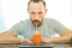 Сок серьезного несчастного человека сидя и выпивая Стоковые Фото