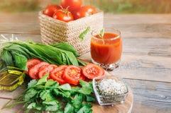 Сок томата, большая ветвь зрелых красных томатов на деревянной доске с листьями укропа ramsonand в деревенском стиле Стоковые Фотографии RF