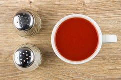 Сок томата в белых чашке, соли и перце на таблице Стоковое Фото