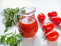 Сок томата полит в стеклянный кувшин с томатами на белизне Стоковая Фотография