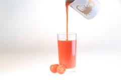 Сок томата подачи потока в прозрачное стекло, стекло t Стоковая Фотография
