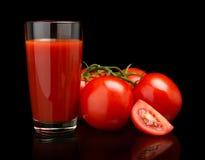 Сок томата с томатами, зеленая хворостина на черноте Стоковое Изображение