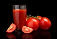 Сок томата с томатами, зеленая хворостина на черноте Стоковая Фотография