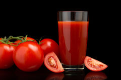 Сок томата с томатами, зеленая хворостина на черноте Стоковая Фотография RF