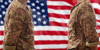 Солдаты в американских воинских цифровых формах картины, стоя на предпосылке флага США Стоковое Фото