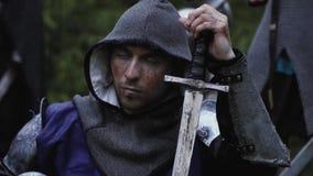 Солдат от средневековых возрастов с клобуком на его голове сидит с его шпагой сток-видео