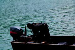 Солдат силуэта на шлюпке в реке с космосом экземпляра добавляет текст Стоковое Изображение RF