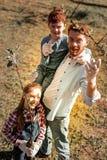 Солнечная милая рыжеволосая усмехаясь семья ища деревья стоковое фото rf