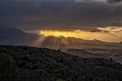 Солнечные лучи спуская через облака Стоковая Фотография