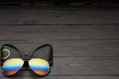 Солнечные очки авиатора лета с отраженными объективами цвета сделали из стекла в рамке металла цвета золота с черным кожаным случ стоковое фото