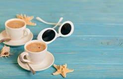 Солнечные очки и 2 белых чашки кофе на деревянном голубом backgro Стоковые Фотографии RF